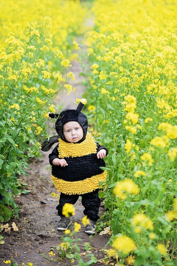 leuk en vrolijk portret van weinig kindzitting in bloeiende bloemen van paardebloem in geel bijenkostuum stock afbeelding