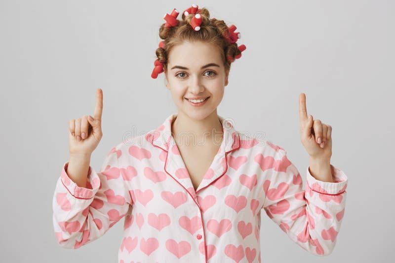 Leuk en vrouwelijk Europees meisje in haar-krulspelden en nachthemden, benadrukkend met wijsvingers, glimlachend en kijkend bij royalty-vrije stock afbeeldingen