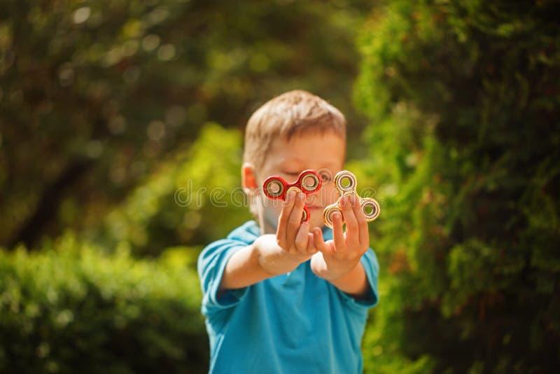 Leuk friemelt weinig jongen die spelen met handspinners in de zomerdag Populair en in stuk speelgoed voor kinderen en volwassene stock afbeeldingen
