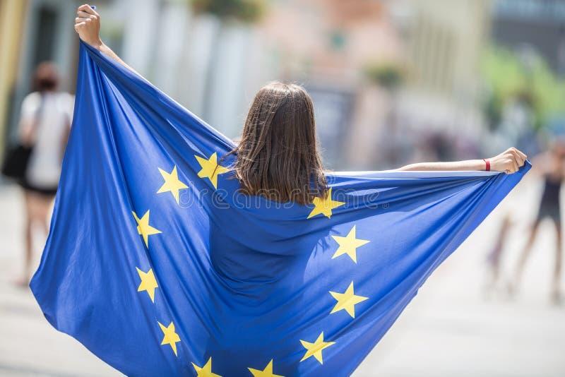 Leuk gelukkig jong meisje met de vlag van de Europese Unie in de straten ergens in Europa stock afbeeldingen