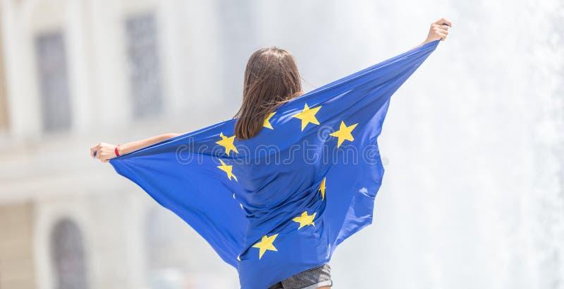 Leuk gelukkig jong meisje met de vlag van de Europese Unie voor een historisch gebouw ergens in Europa stock afbeeldingen