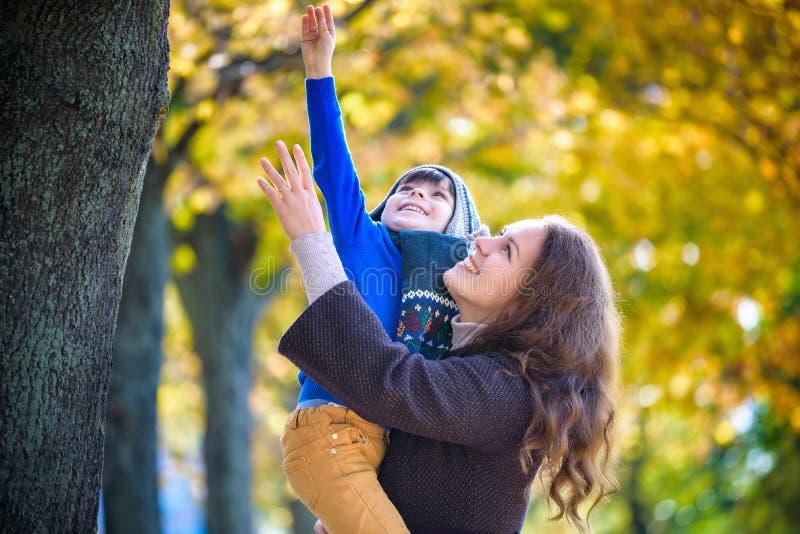 Leuk, gelukkig, jongen die en met zijn mamma onder gele bladeren glimlachen koesteren Weinig kind die pret met moeder in de herfs stock foto