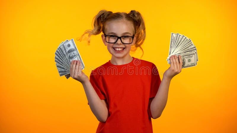 Leuk gelukkig meisje die bossen van dollarcontant geld tonen, wunderkind het winnen toelage, inkomen royalty-vrije stock foto's