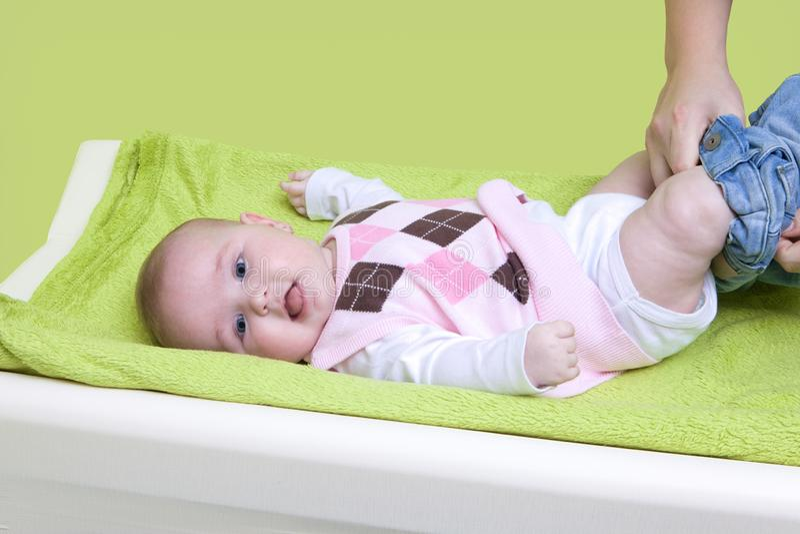 Leuk gelukkig meisje die gekleed worden Moeder die haar baby op veranderend stootkussen kleden Zuigelingsbaby met roze sweater royalty-vrije stock foto