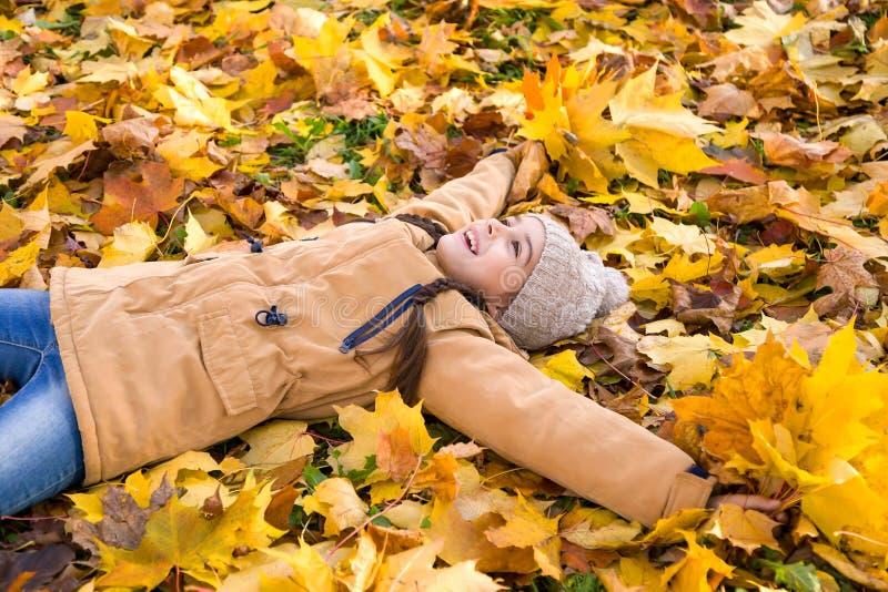 Leuk gelukkig meisje die op de gevallen uitgestrekte bladerenwapens liggen stock foto