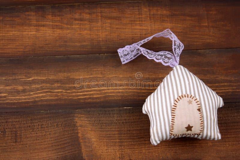 Leuk gestript gevuld stuk speelgoed in een vorm van huis op een houten achtergrond royalty-vrije stock foto