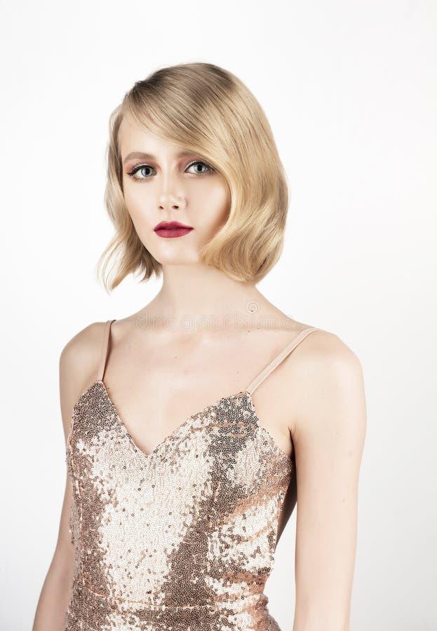Leuk gezichts blond meisje met grote mooie ogen, rode lippen en uitstekend stijlkapsel, die een gouden fonkelende kleding dragen  stock fotografie
