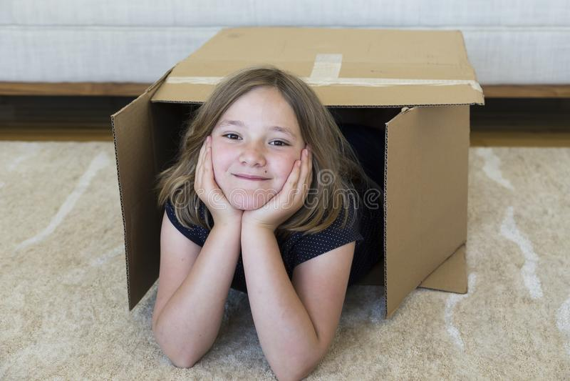 Leuk glimlachend meisje die in de duidelijke bruine doos van het huis bewegende karton liggen royalty-vrije stock foto
