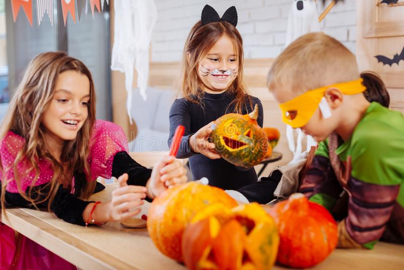 Leuk glimlachend meisje die kattenkostuum dragen die weinig gesneden Halloween-pompoen houden royalty-vrije stock foto