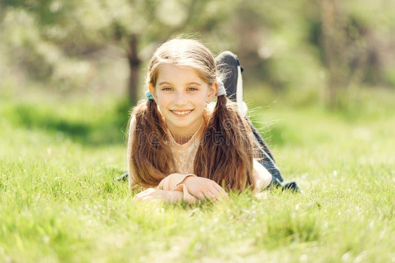 Leuk glimlachend meisje die op het gras liggen stock foto's