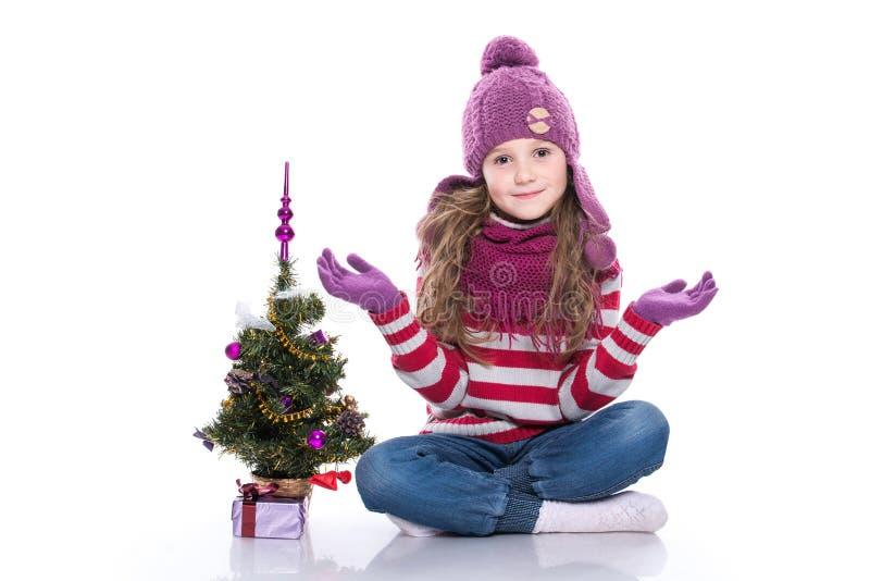 Leuk glimlachend meisje die purpere gebreide sjaal en hoed dragen, zittend dichtbij Kerstmisboom en gift die op witte achtergrond royalty-vrije stock fotografie