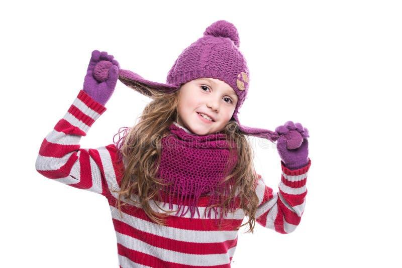 Leuk glimlachend meisje die purpere gebreide sjaal, hoed en handschoenen op witte achtergrond dragen De winterkleren stock foto's