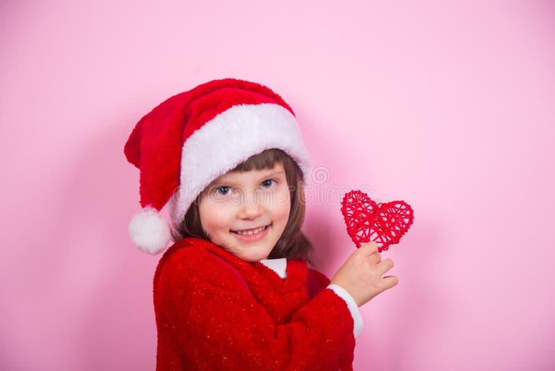 Leuk glimlachend meisje in Kerstmanhoed en Kerstmiskostuum die rood hart in studio op roze achtergrond houden royalty-vrije stock foto's