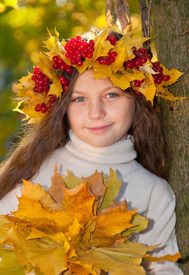Leuk glimlachend meisje in kroon van rode viburnum stock fotografie