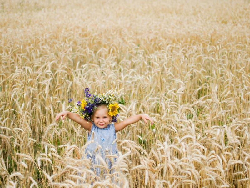 Leuk glimlachend meisje met bloemkroon op de weide bij het landbouwbedrijf Portret van aanbiddelijk klein jong geitje in openluch royalty-vrije stock foto