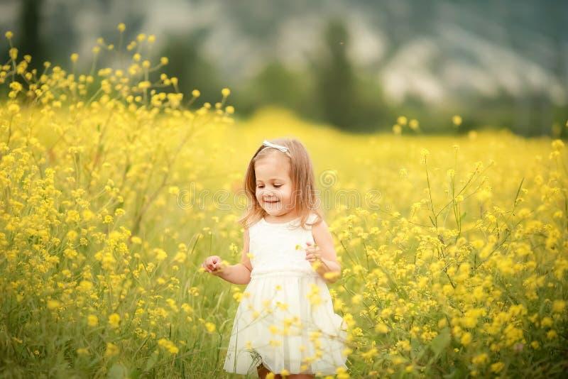 Leuk glimlachend meisje met bloemkroon op de weide bij het landbouwbedrijf Portret van aanbiddelijk klein jong geitje in openluch stock afbeeldingen