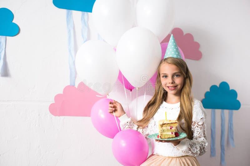 leuk glimlachend meisje in van de de holdingsverjaardag van de partijhoed de cake en de ballons terwijl het kijken stock fotografie