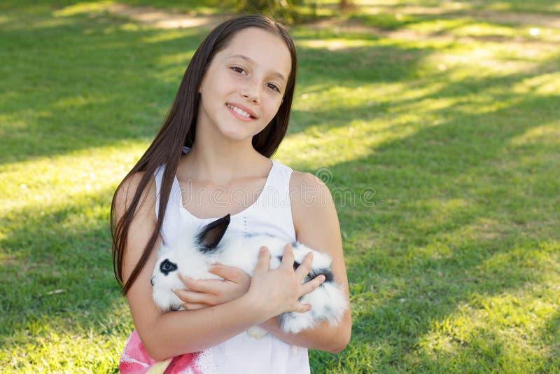 Leuk glimlachend tienermeisje die wit en zwart babykonijn houden stock foto's