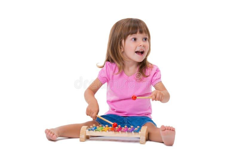 Leuk glimlachend vrolijk positief meisje 3 jaar het oude spelen met muzikale instrumentenstuk speelgoed xylofoon die op witte ach stock afbeeldingen