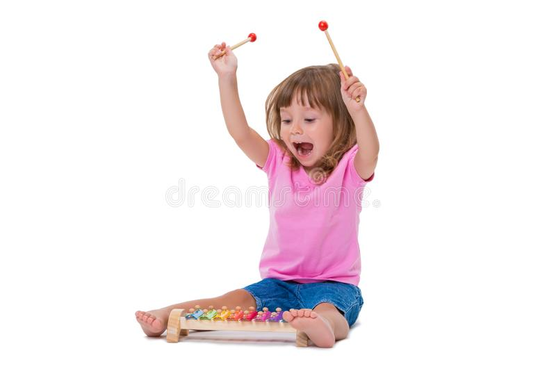 Leuk glimlachend vrolijk positief meisje 3 jaar het oude spelen met muzikale instrumentenstuk speelgoed xylofoon die op witte ach stock fotografie
