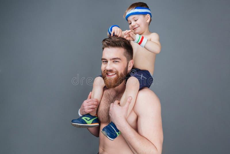 Leuk glimlachend weinig jongenszitting op zijn vaderschouders royalty-vrije stock foto's