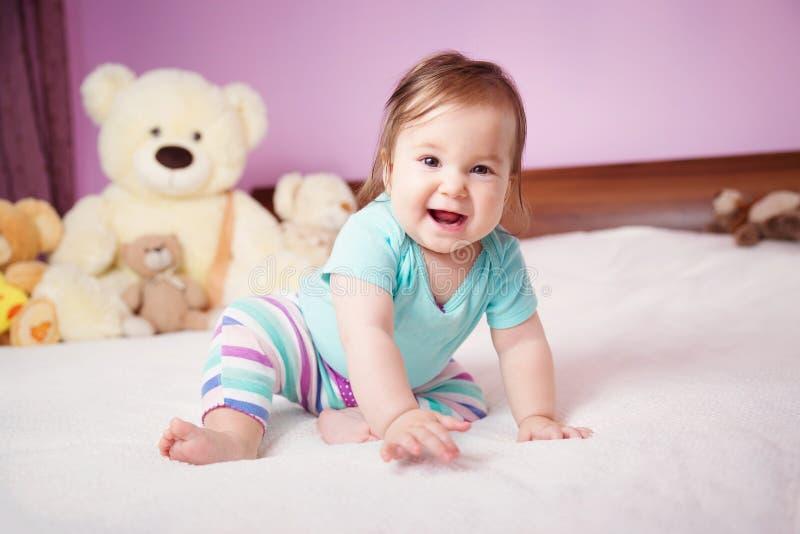 Leuk glimlachend weinig zitting van het babymeisje op het bed met zacht speelgoed royalty-vrije stock fotografie