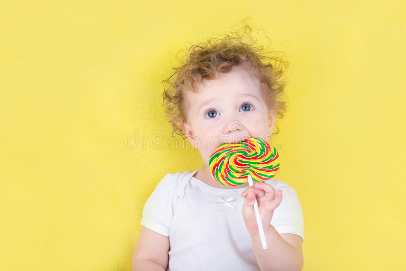 Leuk grappig babymeisje met een groot suikergoed stock foto's