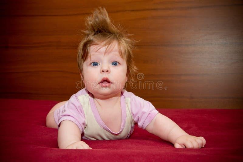 Leuk grappig babymeisje met vrolijk kapsel stock fotografie