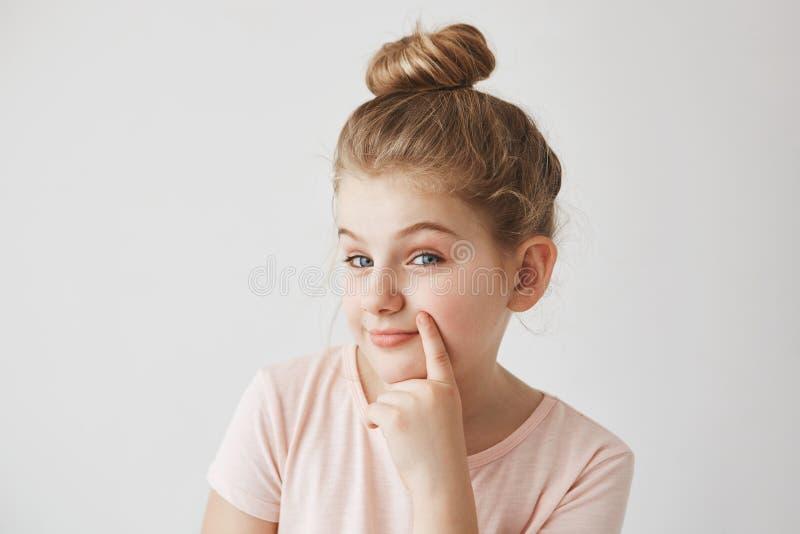 Leuk grappig blond meisje met de holdingsvinger van het broodjeskapsel dichtbij lippen, die in camera en stiekem met opgeheven we royalty-vrije stock foto