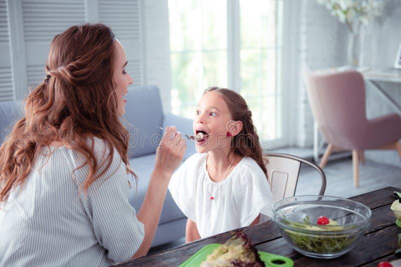 Leuk grappig meisje die haar mond openen terwijl het eten van chocoladedeeg stock afbeelding