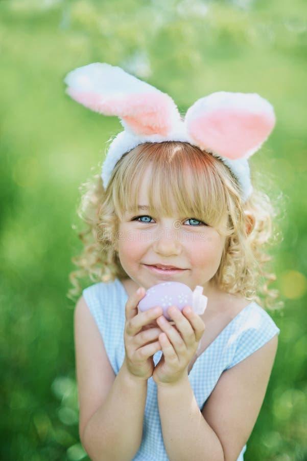 Leuk grappig meisje met paaseieren en konijntjesoren bij tuin Het Concept van Pasen Lachend kind bij paaseijacht stock afbeeldingen