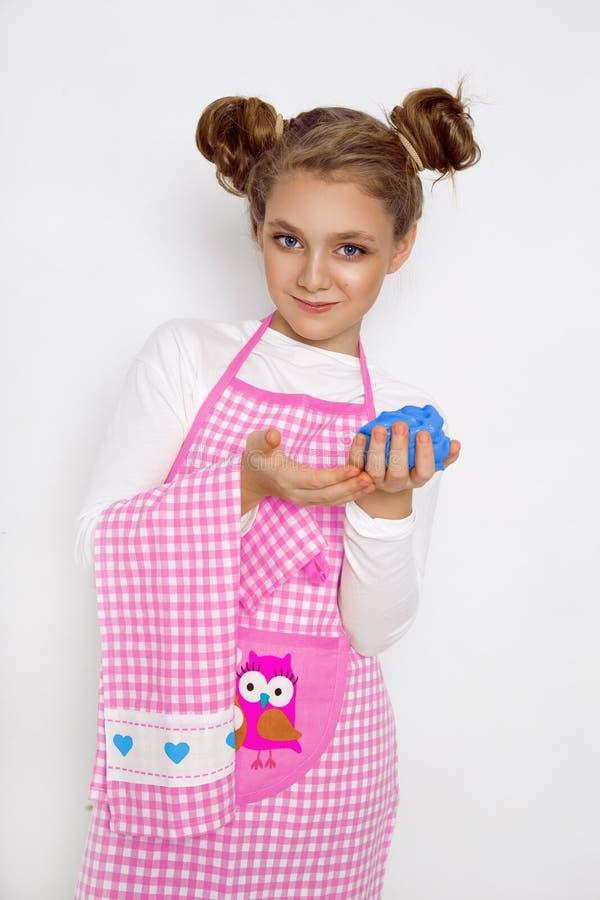 Leuk grappig meisje met slijm in de keuken Het meisje kookt en bakt haar muffins, maakt een cake en een slijm royalty-vrije stock afbeelding