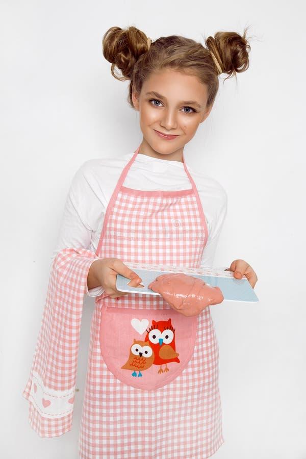 Leuk grappig meisje met slijm in de keuken Het meisje kookt en bakt haar muffins, maakt een cake en een slijm royalty-vrije stock foto
