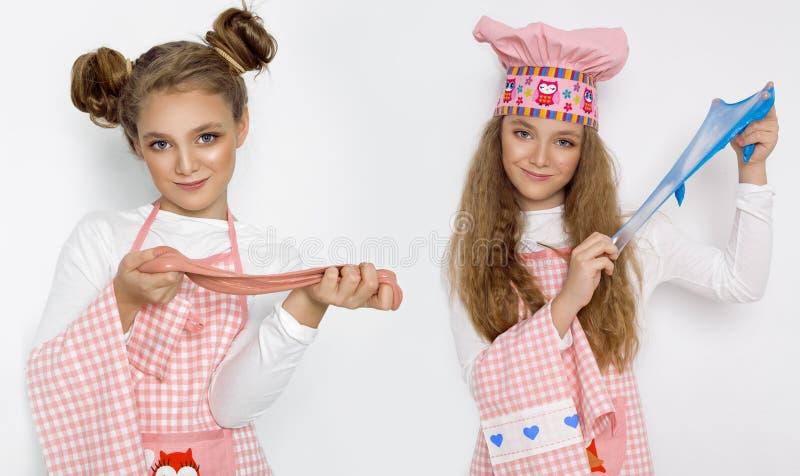 Leuk grappig meisje met slijm in de keuken Het meisje kookt en bakt haar muffins, maakt een cake en een slijm stock afbeelding