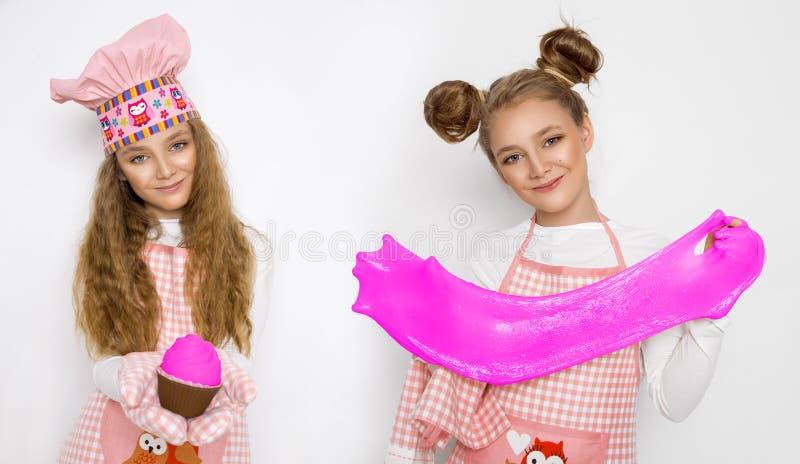 Leuk grappig meisje met slijm in de keuken Het meisje kookt en bakt haar muffins, maakt een cake en een slijm royalty-vrije stock fotografie