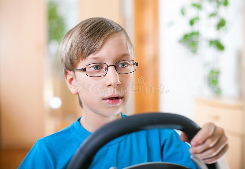 Leuk grappig weinig kind dat bij computer het drijven speelt stock foto's