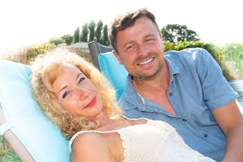 Leuk hoger paar die op poolrand thuis in de zomer liggen royalty-vrije stock foto's