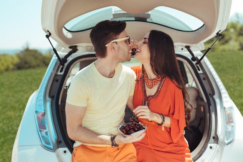 Leuk houdend van paar die zoete kers buiten hun auto samen eten royalty-vrije stock afbeeldingen