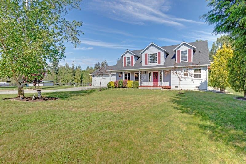 Leuk huis buiten met rode blinden op een de zomerdag stock foto's