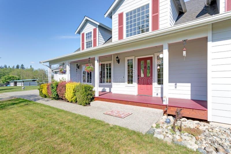Leuk huis buiten met rode blinden op een de zomerdag royalty-vrije stock fotografie