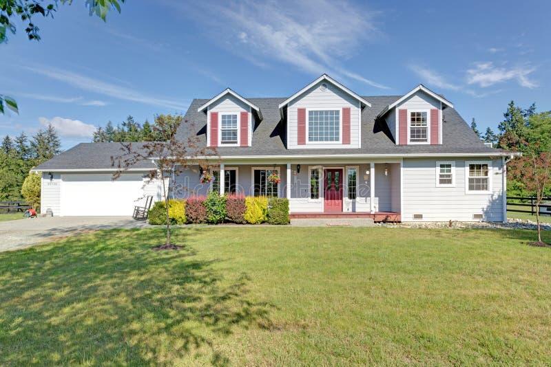 Leuk huis buiten met rode blinden op een de zomerdag stock foto
