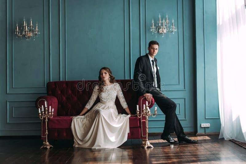 Leuk huwelijkspaar binnen het klassieke studio stellen bij de bank hey kus en omhelzing elkaar, die handen houden bekijkend royalty-vrije stock foto