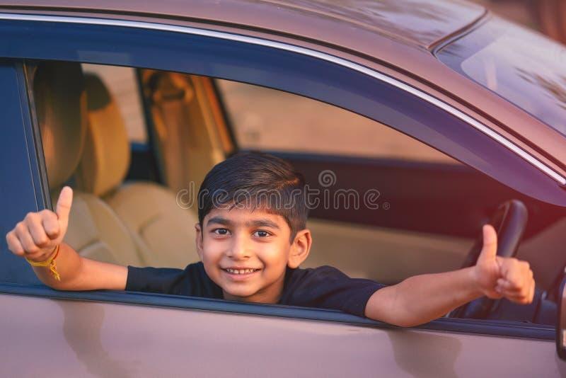 Leuk Indisch kind dat dreunen van autoraam toont royalty-vrije stock foto