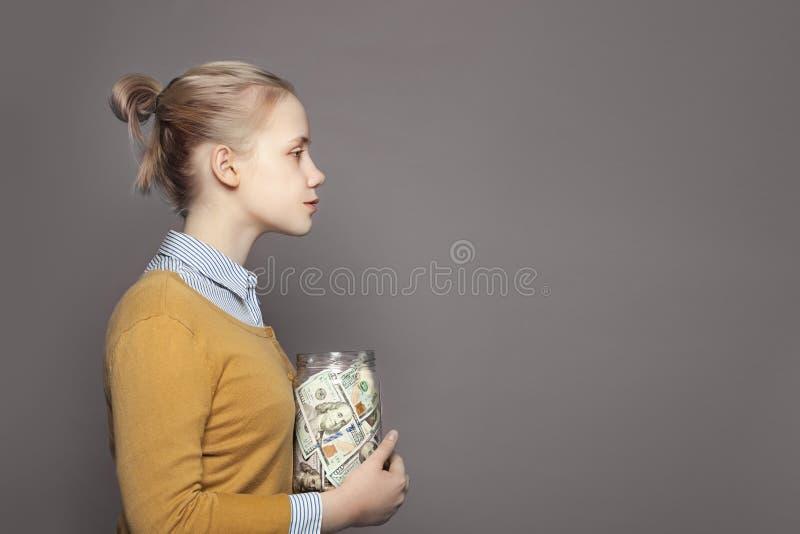 Leuk jong de besparingsgeld van de meisjestiener in glaskruik Onderwijsprijzen en het concept van het besparingsgeld royalty-vrije stock afbeelding