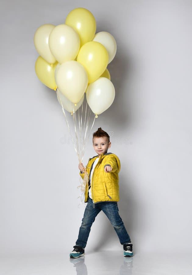 Leuk jong geitje die heel wat ballons houden stock foto
