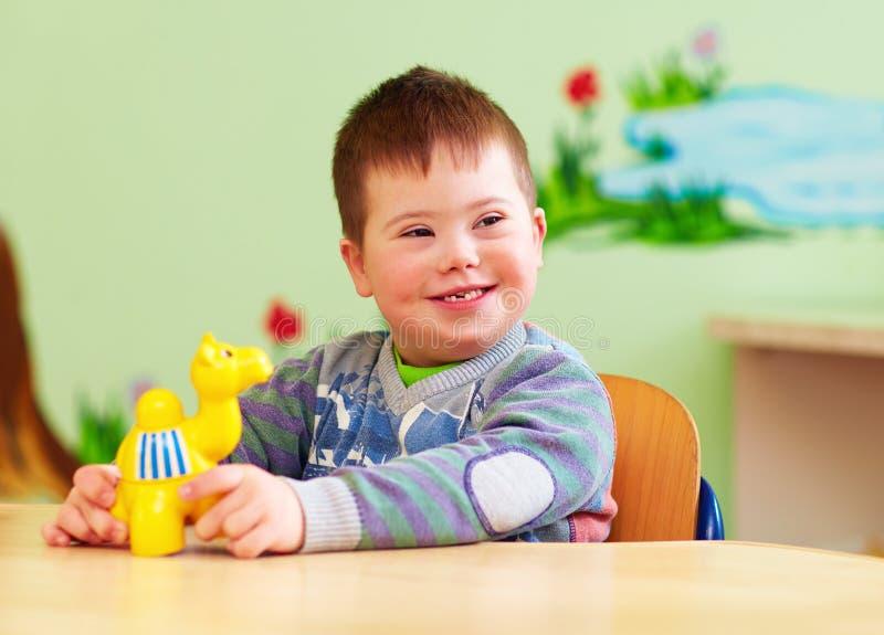 Leuk jong geitje met het beneden het syndroom van ` s spelen in kleuterschool royalty-vrije stock afbeelding