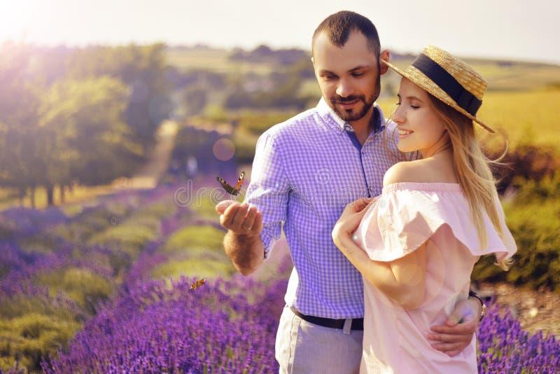 Leuk jong gelukkig paar in liefde op een gebied van lavendelbloemen Geniet van een ogenblik van geluk en liefde op een lavendelge stock foto's