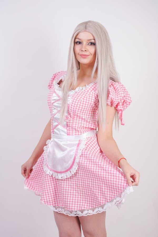 Leuk jong Kaukasisch tienermeisje in roze plaid Beierse kleding met schort het stellen op witte Studio stevige achtergrond royalty-vrije stock foto