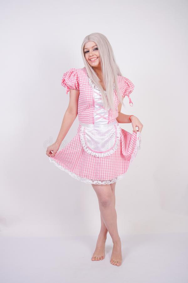 Leuk jong Kaukasisch tienermeisje in roze plaid Beierse kleding met schort het stellen op witte Studio stevige achtergrond stock afbeelding