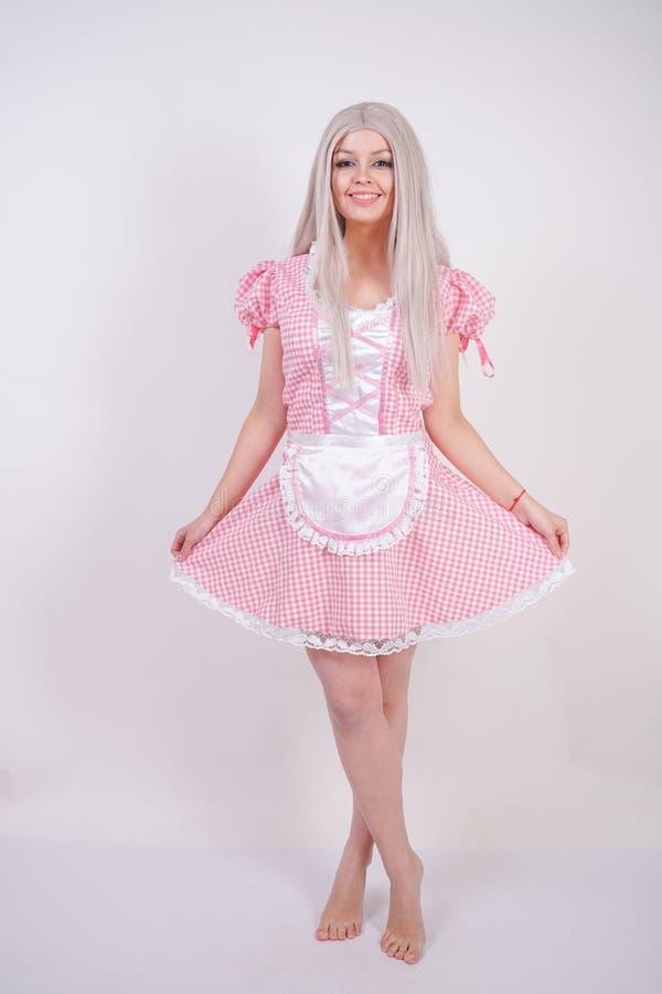 Leuk jong Kaukasisch tienermeisje in roze plaid Beierse kleding met schort het stellen op witte Studio stevige achtergrond royalty-vrije stock foto's